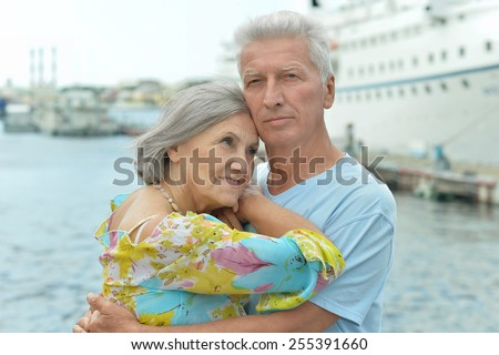 Senior couple standing on pier - stock photo