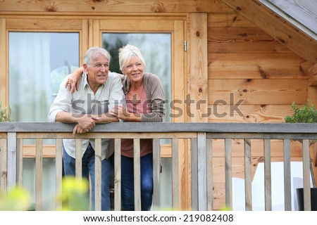 Senior couple standing oustide log cabin in countryside - stock photo