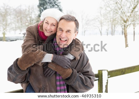 Senior Couple Standing Outside In Snowy Landscape - stock photo