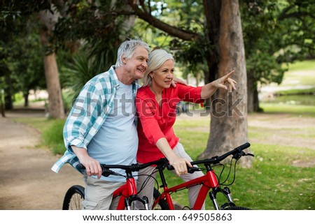 Senior couple standing with bicycle in park on a sunny day