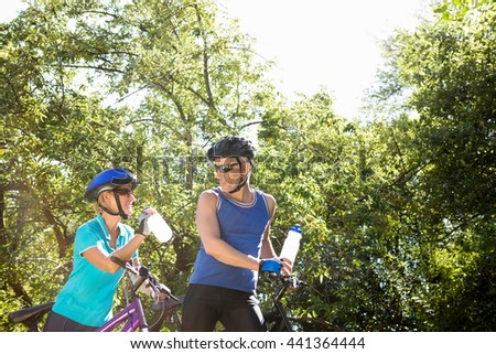 Senior couple standing with their bikes in a forest - stock photo