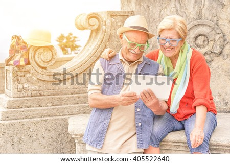 Senior couple surfing online with digital tablet in old european town center - Concept of active elderly and interaction with new technologies - Interaction with new trends and technologies - stock photo