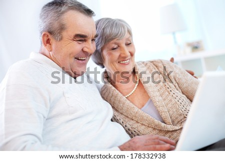 Senior couple surfing the net - stock photo