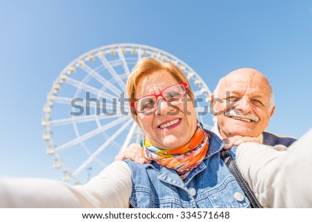 Senior couple taking a selfie at amusement park - Two persons in the 60's having fun with new technologies outdoor - stock photo