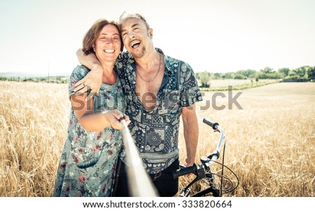 Senior couple taking selfie with stick. concept about adults acting like kids - stock photo