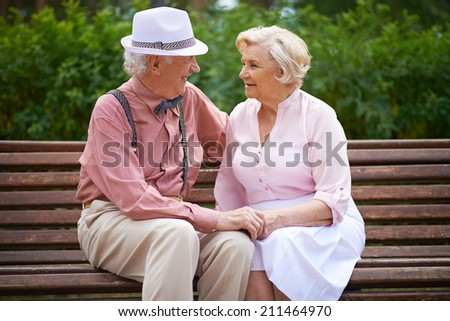 Senior couple talking on bench - stock photo
