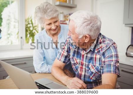 Senior couple talking while using laptop at home - stock photo