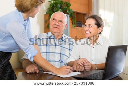 Senior couple talking with employee with laptop at home. Focus on man - stock photo