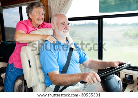 Senior couple traveling in their motor home. The husband is driving. - stock photo