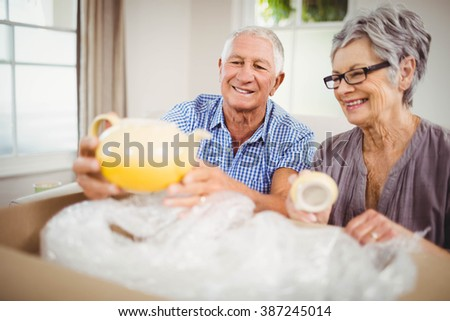 Senior couple unpacking a cardboard box in living room - stock photo