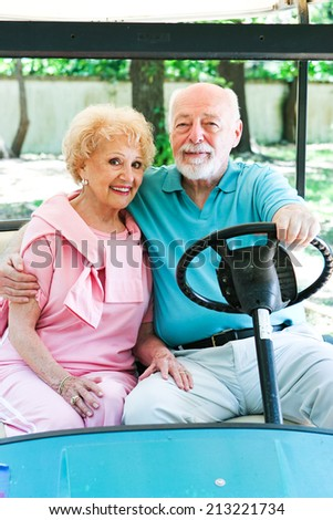 Senior couple uses a golf cart for transportation in their adult community.   - stock photo