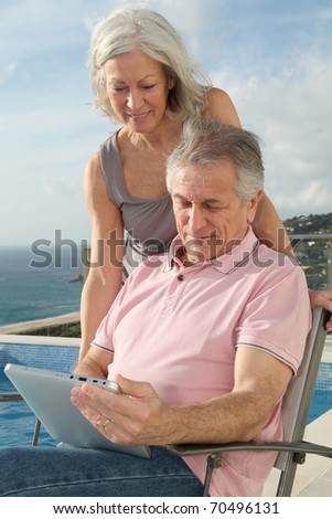 Senior couple using electronic tablet by a swimming-pool - stock photo