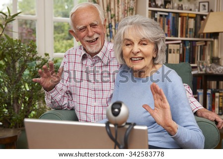 Senior Couple Using Laptop And Webcam To Talk To Family - stock photo