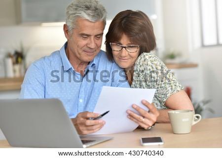 Senior couple using laptop computer at home - stock photo