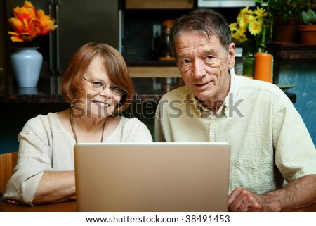 Senior couple using silver laptop computer at home