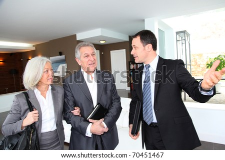 Senior couple visiting modern house with real-estate agent - stock photo