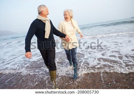 Senior Couple Walking Along Winter Beach - stock photo