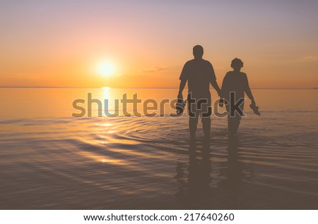 Senior couple walking holding hands in the water at sunset - stock photo