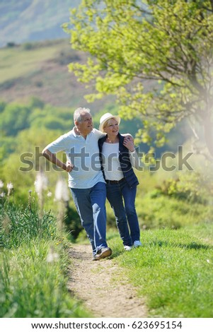Senior couple walking in country track by sunny day