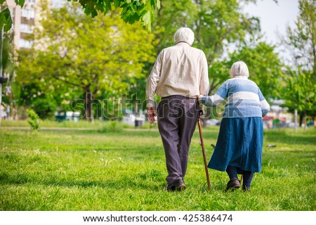 Senior couple walking outdoors in spring - stock photo