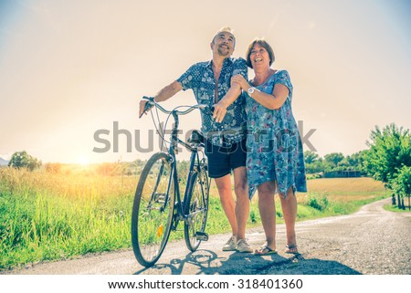 Senior couple walking outdoors, smiling and having fun - Happy cheerful wife and husband riding with a bike on a path in the nature - stock photo