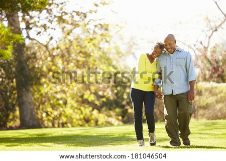 Senior Couple Walking Through Autumn Woodland - stock photo