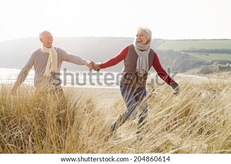 Senior Couple Walking Through Sand Dunes On Winter Beach - stock photo