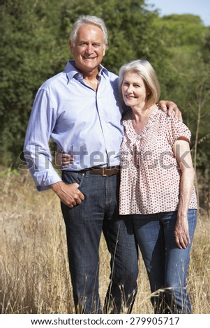 Senior Couple Walking Through Summer Countryside