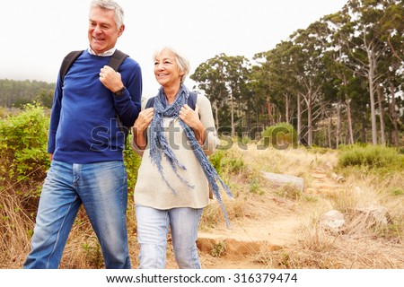 Senior couple walking together in a forest, close-up - stock photo