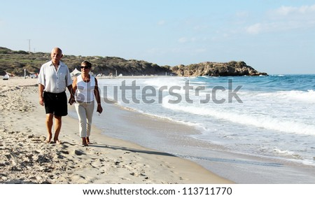 senior couple walking together on a beach - stock photo