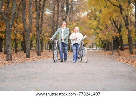 Senior couple walking with bicycles in park