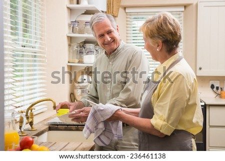 Senior couple washing the dishes at home in the kitchen - stock photo