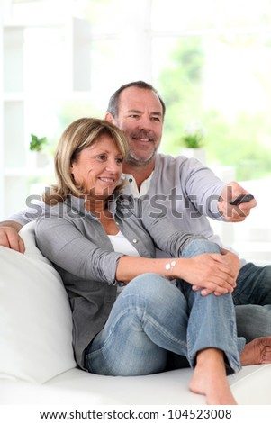 Senior couple watching television at home - stock photo