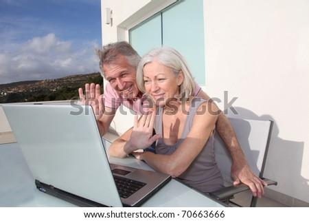Senior couple waving at web-camera on laptop computer - stock photo
