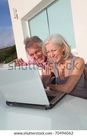 Senior couple waving at webcamera on laptop computer - stock photo