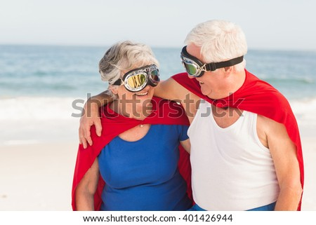Senior couple wearing superman costume on a sunny day - stock photo