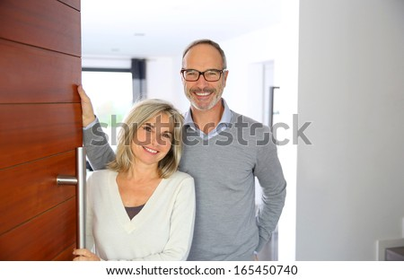 Senior couple welcoming people to enter home - stock photo