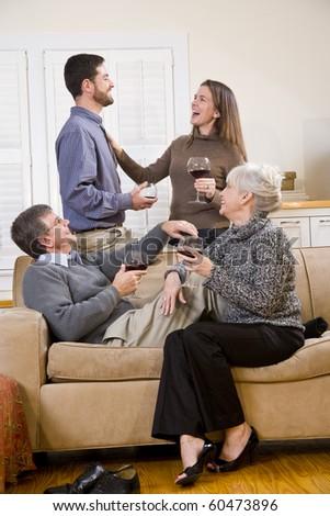 Senior couple with adult children conversing and drinking wine