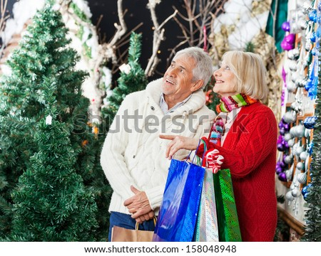 Senior couple with bags shopping at Christmas store - stock photo