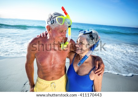 Senior couple with beach equipment at the beach