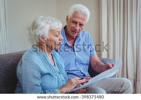 Senior couple with bills while sitting on sofa at home - stock photo