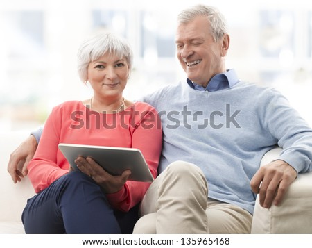 Senior couple with digital tablet surfing on the internet at home - stock photo