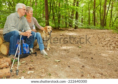 Senior couple with dog sitting in a forest on tree logs - stock photo