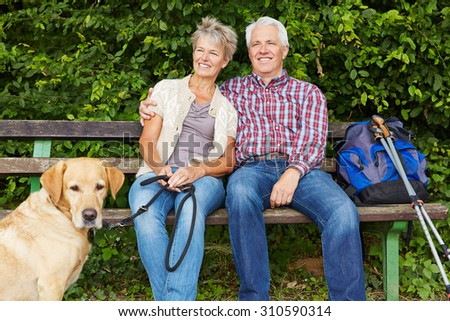 Senior couple with dog sitting on bench while hiking in nature - stock photo
