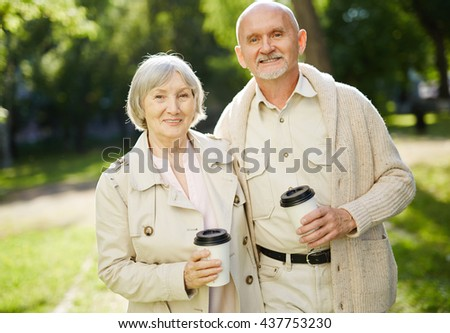 Senior couple with drinks spending time in park - stock photo