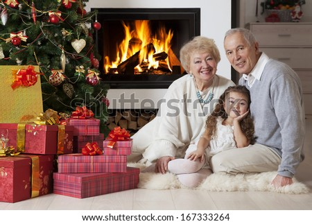 Senior couple with granddaughter enjoying Christmas in front of fireplace  - stock photo