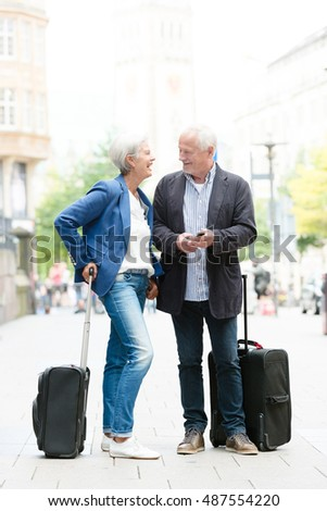 Senior couple with  suitcases and cell