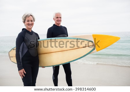 Senior couple with surfboard standing on the beach on a sunny day - stock photo