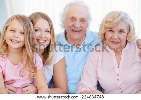Senior couple with their daughter and granddaughter looking at camera with smiles - stock photo