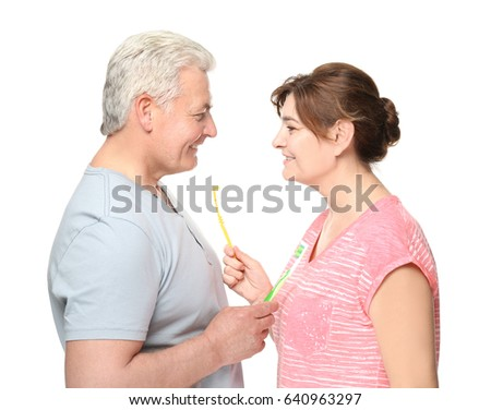 Senior couple with toothbrushes on white background